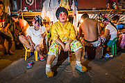 "19 AUGUST 2014 - BANGKOK, THAILAND:  Members of the cast of the Lehigh Leng Kaitoung Opera troupe relax backstage before a performance near the Chaomae Thapthim Shrine, a small Chinese shrine in a working class neighborhood of Bangkok. The performance was for Ghost Month. Chinese opera was once very popular in Thailand, where it is called ""Ngiew."" It is usually performed in the Teochew language. Millions of Chinese emigrated to Thailand (then Siam) in the 18th and 19th centuries and brought their culture with them. Recently the popularity of ngiew has faded as people turn to performances of opera on DVD or movies. There are still as many 30 Chinese opera troupes left in Bangkok and its environs. They are especially busy during Chinese New Year and Chinese holiday when they travel from Chinese temple to Chinese temple performing on stages they put up in streets near the temple, sometimes sleeping on hammocks they sling under their stage. Most of the Chinese operas from Bangkok travel to Malaysia for Ghost Month, leaving just a few to perform in Bangkok.        PHOTO BY JACK KURTZ"