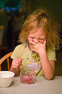 little girl covering her mouth while giggling and eating