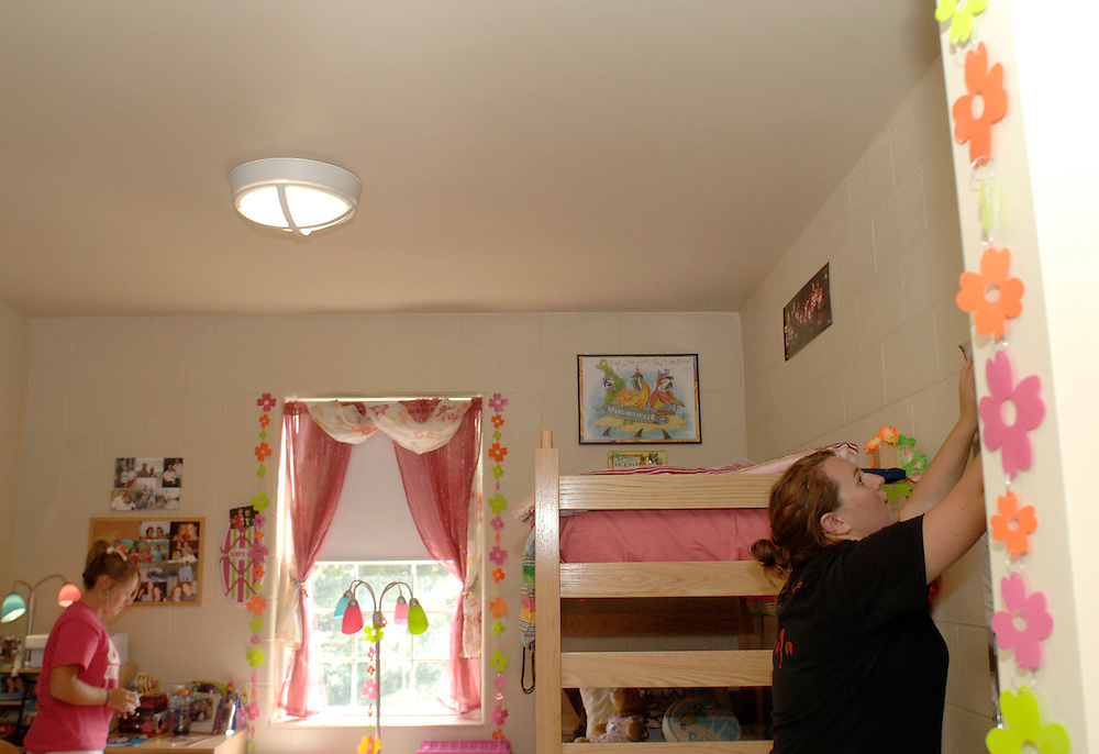 Ohio Univesity sophomores Courtney Kirchoff (left) and Lindsay Stewart decorate their room in Adams Hall Sunday afternoon.