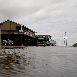 A road leading to several camps is flooded from rising seas due to Hurricane Alex in Grand Isle, Louisiana, U.S., on Wednesday, June 30, 2010. The BP Plc oil spill, which began when the leased Transocean Deepwater Horizon oil rig exploded on April 20, is gushing as much as 60,000 barrels of oil a day into the Gulf of Mexico, the government said. Photographer: Derick E. Hingle/Bloomberg