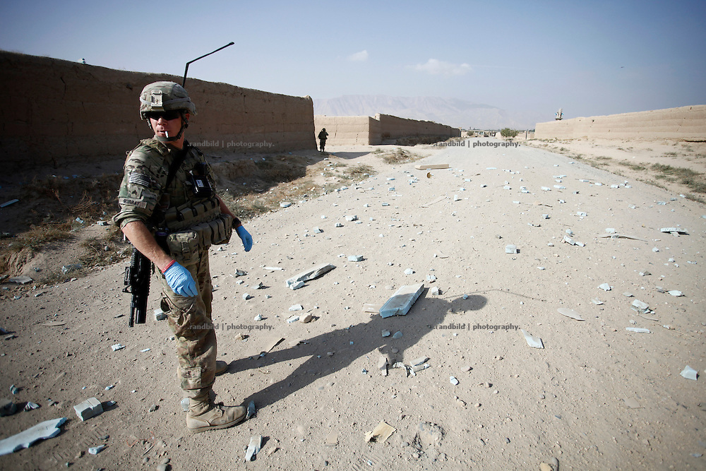A service member of a RCP stands on a road in Nawabad shortly after his Unit was hit by an IED.  A Route Clearance Package patrols to identify hidden IED´s along a certain road.