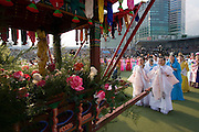 The annual Lotus Lantern Festival is held to celebrate Buddha's Birthday. Opening ceremony for the parade at Dongdaemun Stadium. Buddha statue, symbolically bathed with water at the end of the ceremony, and being readied to be carried in the parade.