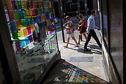 Passers-by walk past coloured light from a corner cafe reflected on the pavement in Fleet Street in the City of London, the capital's financial district (aka the Square Mile), on 22nd August 2019, in London, England.