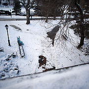 Waiting for a Client…A street performer, dressed as the Statue of Liberty, sits in the freezing cold on a park bench in Central Park awaiting a client after snowfall in the park. Central Park, Manhattan, New York, USA. Photo Tim Clayton