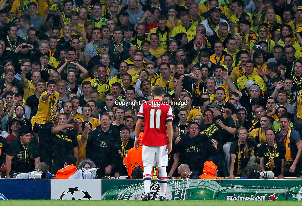 epa03919929 Mesut Oezil of Arsenal stands in fornt of Borussia Dortmund supporters during the UEFA Champions League match between Arsenal London and Borussia Dortmund in London, Britain, 22 October 2013.  EPA/KERIM OKTEN