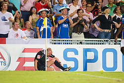 Hong Kong, China - Friday, July 27, 2007: The assistant lines-man lies injured after a tackle from Portsmouth's Djimi Traore during the final of the Barclays Asia Trophy at the Hong Kong Stadium. (Photo by David Rawcliffe/Propaganda)