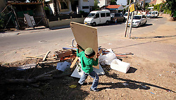 Sderot  - May 2nd ,  2008 -   A young boy removes some wood from a pile of rubbish in Sderot, Southern Israel, The small town has frequent rocket attacks from Gaza, May 2nd, 2008. Picture by Andrew Parsons / i-Images