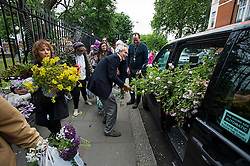 © London News Pictures. 23/05/2015. London, UK. Large plants being loaded in to a taxi. Members of the public carry exhibitors' plants from the 2015 Chelsea Flower show, which ends today (Sat). The Royal Horticultural Society flagship flower show has been held at the Royal Hospital in Chelsea since 1913. Photo credit: Ben Cawthra/LNP