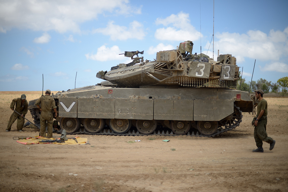 UNSPECIFIED, ISRAEL - JULY 17, 2014: Israeli soldiers work on a Merkava tank, at an army deployment area near Israel's border with the Gaza Strip, on July 17, 2014. Photo by Gili Yaari. /FLASH90