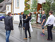 In the village of Zederhaus, the prangstangen are brought to town June 23, the night before the church honors John the Baptist. A young man hoists and carries each 170 pound pole to the church doorway, where he's greeted by the parish priest. It takes a team to turn the giant towers sideways and carry them into the church.