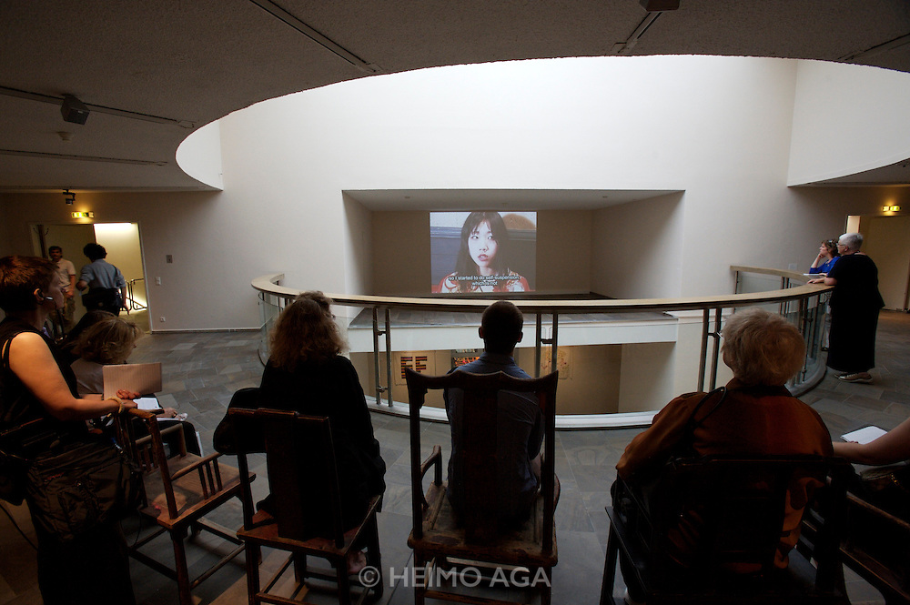 """documenta12. Fridericianum. Visitors are sitting on some of Ai Weiwei's 1001 chairs while watching """"Lovely Andrea"""" by Hito Steyerl about Japanese bondage art."""