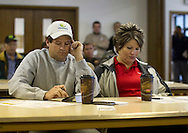 Travis Wearda (from left) and his wife Stacy Wearda, of Duncombe, Iowa, work out the numbers before placing a bid during a farm auction at the Eagle Grove Masonic Lodge in Eagle Grove, Iowa on Thursday, October 18, 2012.