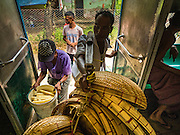 26 OCTOBER 2015 - YANGON, MYANMAR:  A basket vendor gets on the Yangon Circular Train at the Pa Ywet Kone Station. The Yangon Circular Railway is the local commuter rail network that serves the Yangon metropolitan area. Operated by Myanmar Railways, the 45.9-kilometre (28.5 mi) 39-station loop system connects satellite towns and suburban areas to the city. The railway has about 200 coaches, runs 20 times daily and sells 100,000 to 150,000 tickets daily. The loop, which takes about three hours to complete, is a popular for tourists to see a cross section of life in Yangon. The trains run from 3:45 am to 10:15 pm daily. The cost of a ticket for a distance of 15 miles is ten kyats (~nine US cents), and for over 15 miles is twenty kyats (~18 US cents).    PHOTO BY JACK KURTZ