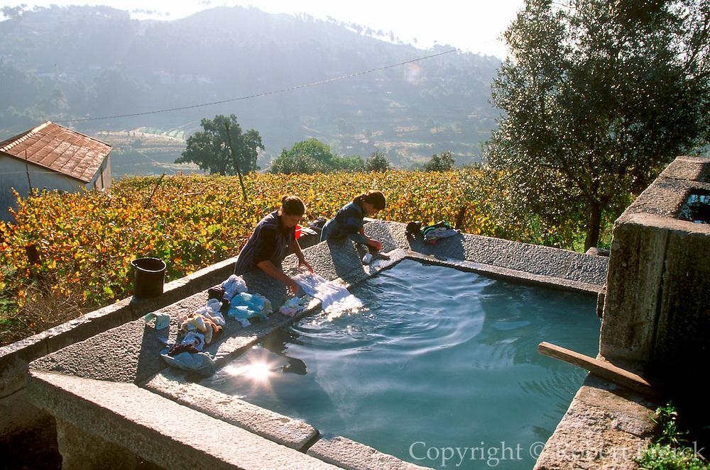 PORTUGAL, NORTH, DOURO RIVER washing clothes at the village fountain near Santa Marinha, east of Peso da Regua in the Douro River valley