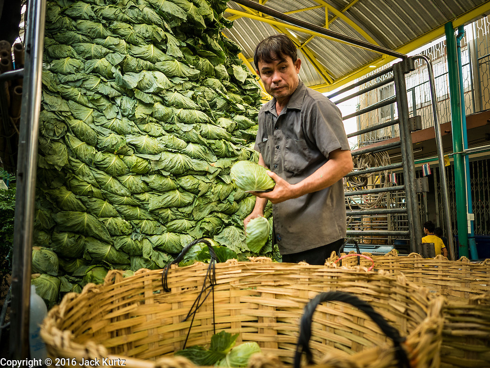 "11 AUGUST 2016 - BANGKOK, THAILAND:  A worker unloads a truck of cabbage in the produce section of Pak Khlong Talat in Bangkok. Pak Khlong Talat (literally ""the market at the mouth of the canal"") is the best known flower market in Thailand. It is the largest flower market in Bangkok. Most of the shop owners in the market sell wholesale to florist shops in Bangkok or to vendors who sell flower garlands, lotus buds and other floral supplies at the entrances to temples throughout Bangkok. There is also a fruit and produce market which specializes in fresh vegetables and fruit on the site. It is one of Bangkok's busiest markets and has become a popular tourist attraction.         PHOTO BY JACK KURTZ"
