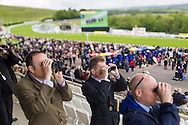 Race goers watch the 32 Red.com Stakes during day three of the May Festival at Goodwood Racecourse, Chichester. PRESS ASSOCIATION Photo. Picture date: Saturday May 24, 2014. See PA story RACING Goodwood. Photo credit should read: Chris Ison/PA Wire. Editor's note: The image shot on a tilt shift perspective control lens.