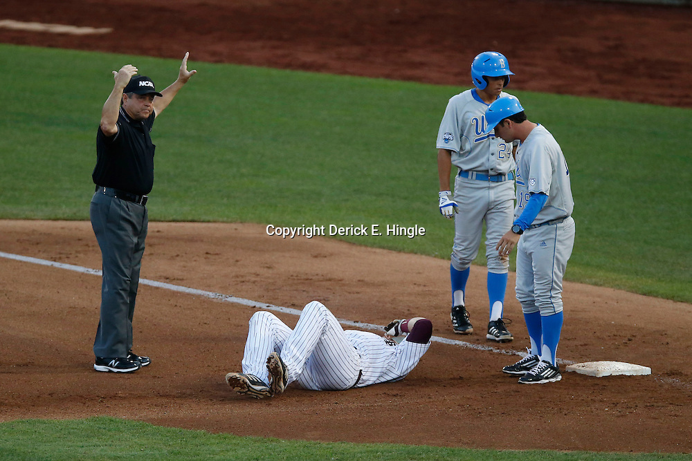 Jun 24, 2013; Omaha, NE, USA; Mississippi State Bulldogs first baseman Wes Rea (bottom) lays on the ground after a collision with UCLA Bruins center fielder Brian Carroll (24) during the fourth inning in game 1 of the College World Series finals at TD Ameritrade Park. Mandatory Credit: Derick E. Hingle-USA TODAY Sports
