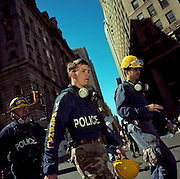 During a journey into America's hinterlands, days after the September 11th attacks in New York and Washington DC, a team of New York City Police Department (NYPD) and a US Marshal walks through a barrier after spending a traumatic shift searching for human remains in the 'Pile' of Ground Zero. Making their way through the general public, they have a look of exhaustion and stress. Haunted but still mindful of the enormous task ahead to investigate the crimes committed here, they go towards a welcome rest. The streets are tall above them and the sky a clear blue as the men carry their hard hats with dust masks still around their necks - protection from the then unknown hazardous elements and chemicals in the environment.