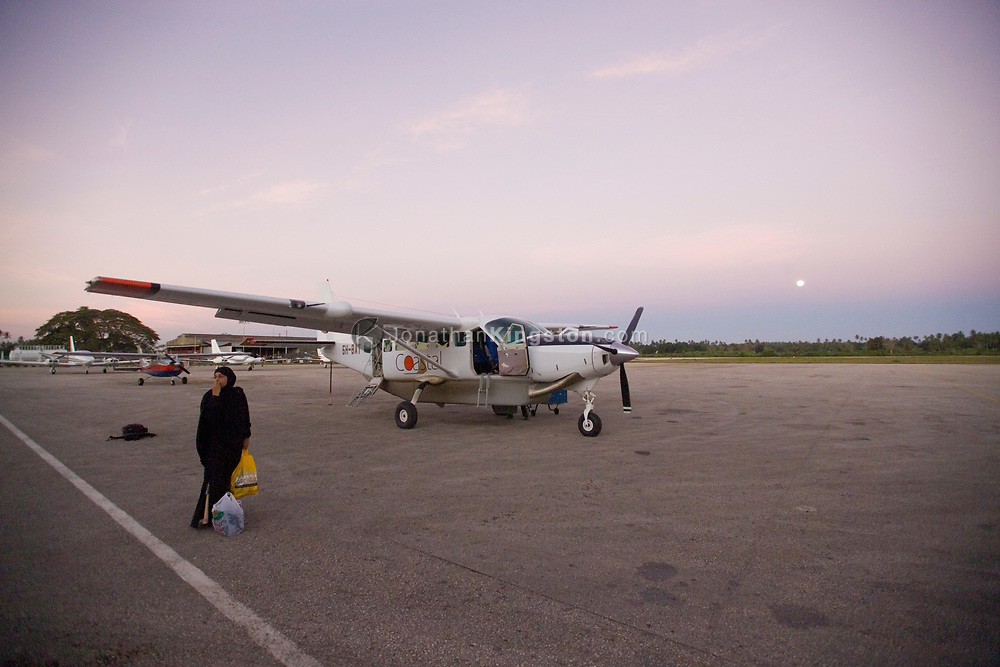 A woman waits with bags outside of a small engine airplane at the Zanzibar Kisauni International Airport. Chukwani, Zanzibar, Tanzania.