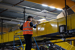 """© Licensed to London News Pictures . 04/12/2019. Manchester , UK . A member of warehouse staff uses a pole to dislodged empty boxes that have become jammed on a conveyor belt inside the """"MAN1"""" Amazon fulfilment centre warehouse at Manchester Airport in the North West of England . Photo credit : Joel Goodman/LNP"""