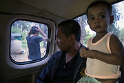 Supot Kalasong, 42, leaves the village in a pickup with his son to travel to Bangkok to submit a document to a government office. In April 2016 Mr Kansong was shot in 6 places by an assassin who had been waiting for him to drive past as he returned to the village. He remarkably survived.<br /> <br /> Since 2008, this community of around 70 families have been embroiled in a conflict with a palm oil company that locals allege has been trying to violently evict them. Since 2010, four members of the community have been shot dead and a fifth shot, but survived.<br /> <br /> For decades the palm oil company Jiew Kang Jue Pattana Co., Ltd has illegally occupied and cultivated palm oil trees on a 535-acre plot of land in the Chai Buri District of Surat Thani Province. <br /> <br /> The company operated with no official legal documentation or land concession, until the Southern Peasant's Federation of Thailand (SPFT), who supports the community, began investigating them and collecting evidence.<br /> <br /> This evidence ultimately lead to a Supreme Court ruling against the company for illegal trespassing and land encroachment. But the community still struggles to remain on the land to this day with the last shooting happening in April 2016, years after the court case was won.