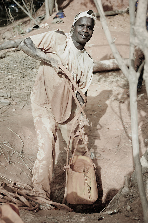 Stock photograph of an African gold miner in Guinea hauling a bag of ore up from the shaft.