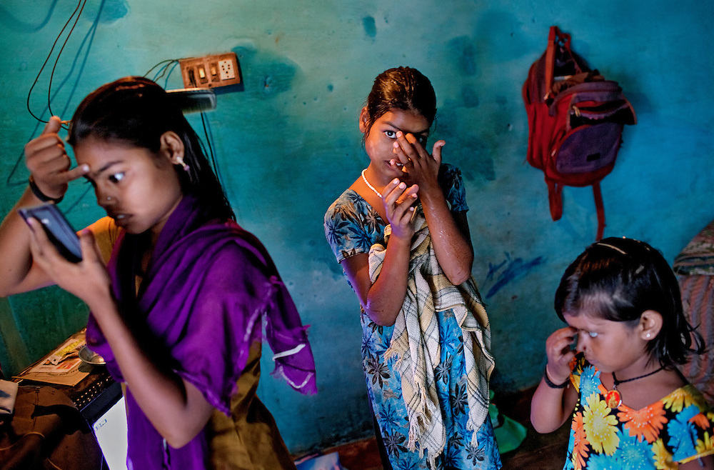 Poonam, 11, (centre) her oldest sister Arti, 17, (left) and their young friend Dipshika, 4, (right) are applying a Bindi decoration to their forehead, while inside the family's newly built home in Oriya Basti, one of the water-contaminated colonies in Bhopal, central India, near the abandoned Union Carbide (now DOW Chemical) industrial complex, site of the infamous '1984 Gas Disaster'. A Bindi is a forehead decoration worn in South Asia, traditionally a bright red dot, applied between the eyebrows.