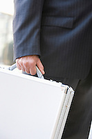 Businessman with briefcase, mid section