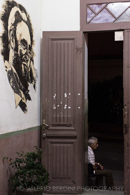 A school keeper sits on the doorway of a primary school entrance in Cienfuegos at night. A Fidel Castro mural is inside the hall. Despite the school is closed, there are keeper looking after government building at all time during the day and night. Cuba, 2015