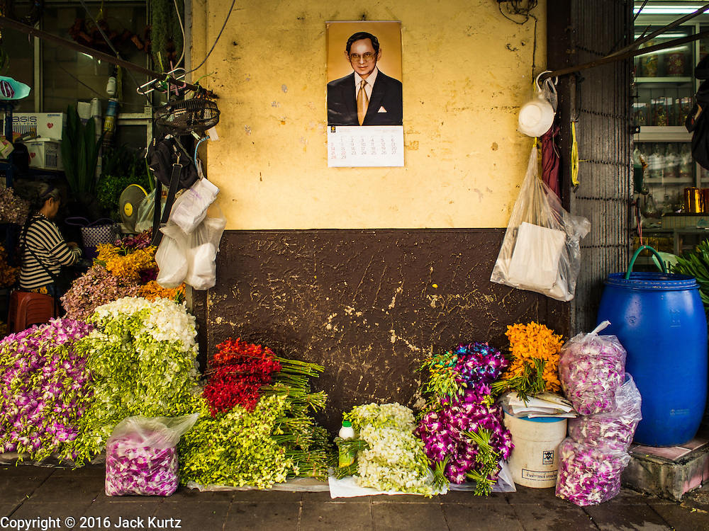 29 FEBRUARY 2016 - BANGKOK, THAILAND: Flowers for sale on the sidewalk under a portrait of Bhumibol Adulyadej, the King of Thailand, near the Bangkok flower market. This used to be a large sidewalk stand but now is just some flowers on the sidewalk. Many of the sidewalk vendors around Pak Khlong Talat, the Bangkok flower market, closed their stalls Monday. As a part of the military government sponsored initiative to clean up Bangkok, city officials announced new rules for the sidewalk vendors that shortened their hours and changed the regulations they worked under. Some vendors said the new rules were confusing and too limiting and most vendors chose to close Monday rather than risk fines and penalties. Many hope to reopen when the situation is clarified.    PHOTO BY JACK KURTZ
