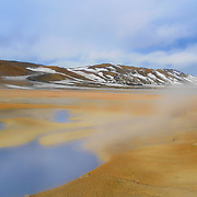 Námafjall is a mountain near Mývatn in the North East of Iceland. The mountain is close to the Kraftla volcano and is right in the middle of a geothermal area. The mountain is hot and the snow melts much quicker on Námafjall. Hverir is a hot-spring area at the base of Námafjall. There is a collection of steam fumaroles, some bubbling mud pots and lots of interesting colours.