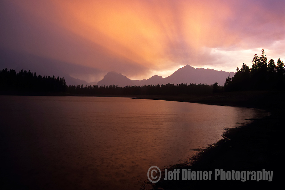 A fiery sunset rainstorm passes over Jackson Lake in Grand Teton National Park, Jackson Hole, Wyoming.