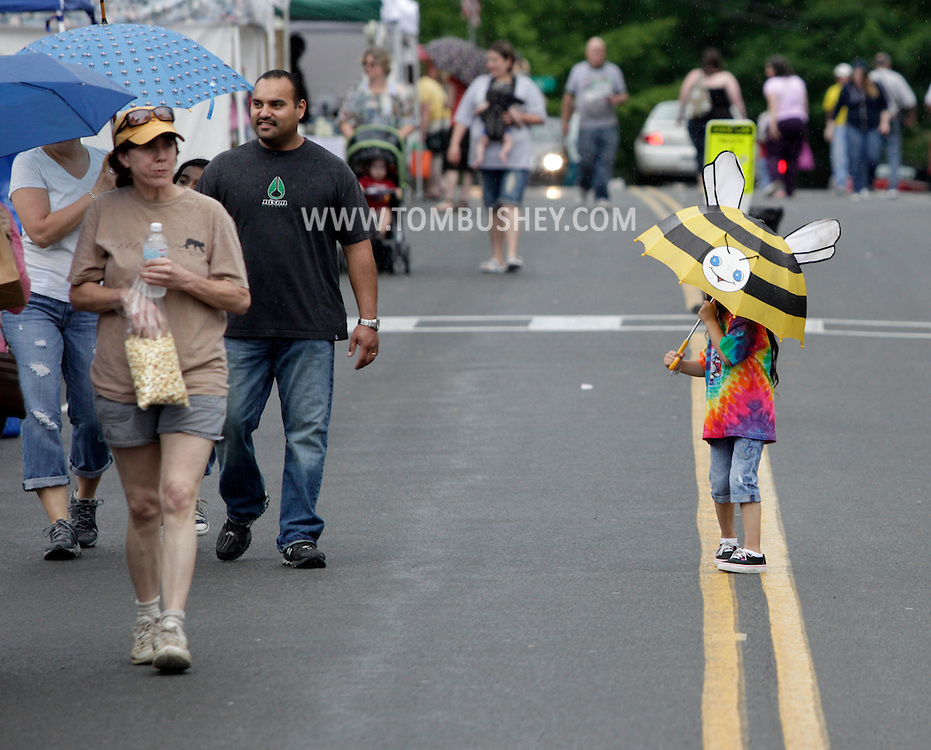 Sugar Loaf, New York - People, including a little girl with a bumble bee umbrella, walk on the closed street during the Sugar Loaf Spring Festival on May 21, 2011.