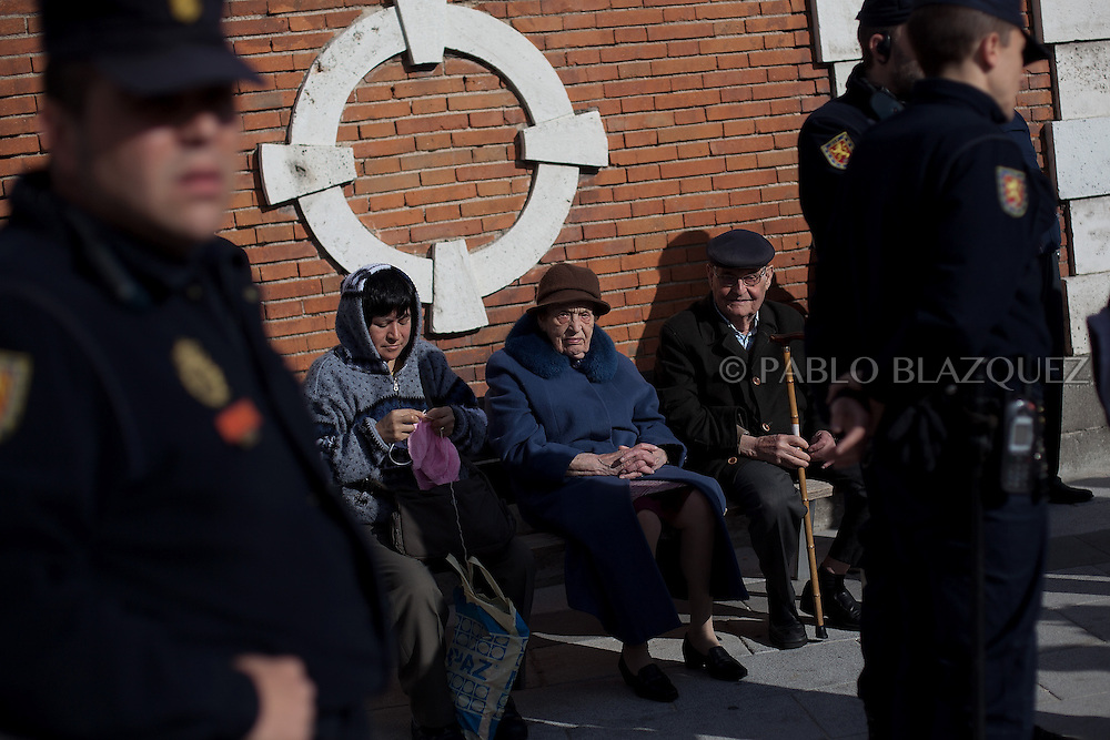 People sit on a bench while riot police stand guard before protesters make their way to an 'escrache' outside the house of PP deputy Beatriz Rodriguez Salmones on April12, 2013 in Madrid, Spain. The Mortgage Holders Platform (PAH) and other anti evictions organizations have been organizing 'escraches' for several weeks under the slogan 'There are lives at risk' to claim the vote for a Popular Legislative Initiative (ILP) to stop evictions and facilitate social rent, outside Popular Party deputies' houses and offices. 'Escraches' are a form of peaceful protest that were used in Argentine in 1995 to publically denounce pardoned members of the dictatorship for their crimes at their doorsteps.