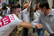 Taro Yamamoto,  a former actor and politician,greets supporters by touching elbows in efforts to not spread  against COVID-19 infection as he campaigns  for election as the Tokyo Governor in Futaka Tamagawa, Tokyo, Japan. Tuesday June 23rd 2020. The incumbent  governor, Yuriko Koike (not pictured) is expected to be reelected when the election are held on Sunday July 5th 2020