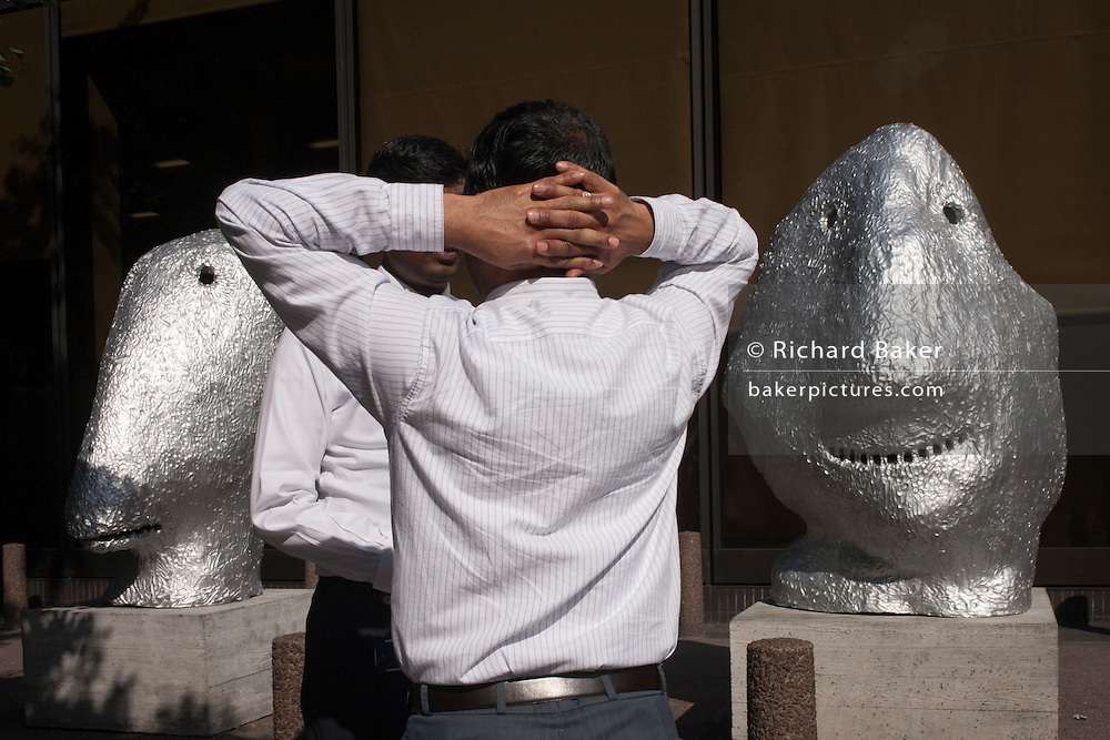 Two businessmen talk next to outdoor art, one with hands and fingers interlocked behind his back in the City of London, UK.