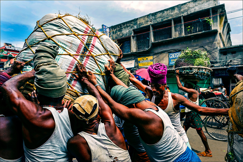 "Called ""human forklifts,"" porters from India's Bihar state wrestle bundles weighing hundreds of pounds onto the turban-wrapped heads of fellow workers at the Kolay Market in the decrepit metropolis of Calcutta in West Bengal. Many Indians fear the entry of giant retailers such as Walmart and Tesco, with their state-of-the-art supply chains, would threaten traditional markets wholesale markets and retail shops.  © Steve Raymer / National Geographic Creative"
