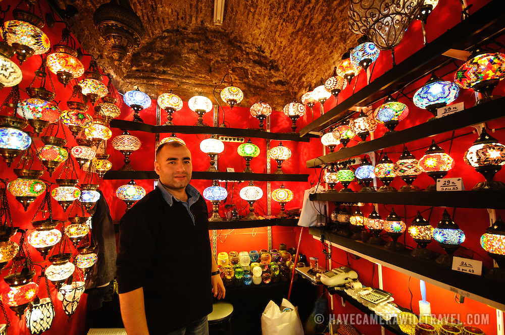 One of the shopkeepers of Istanbul's Grand Bazaar poses for a photo. Istanbul's Grand Bazaar includes many stores selling brightly colored hanging lights with a teardrop design of colorful glass mosaics.