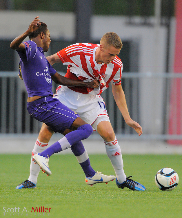 Orlando City Lions forward Dennis Chin (15) grabs the jersey of Stoke City Potters defender Ryan Shawcross (17) as they fight for a ball during their match at the Florida Citrus Bowl on July 28, 2012 in Orlando, Florida. Stoke won the game 1-0...Scott A. Miller/ACTION IMAGES.