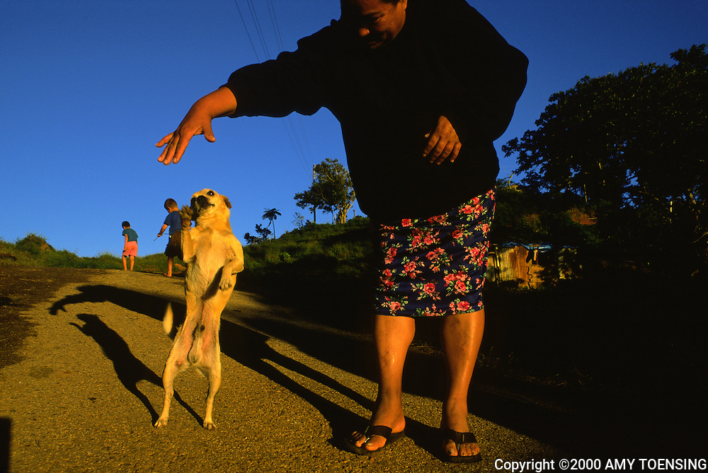 ADJUNTAS, PR - NOVEMBER 18: A woman plays with her dog November 18, 2000 in Adjuntas, Puerto Rico. Puerto Rico was an outpost of Spanish colonialism for 400 years, until the United States took possession in 1898. Today Puerto Rico's Spanish-speaking culture reflects its history - a mix of African slaves, Spanish settlers, and Taino Indians. Puerto Ricans fight in the U.S. armed forces but are not entitled to vote in presidential elections. They passionately debate their relationship with the U.S. with about half the island wanting to become the 51st state and the other half wanting to remain a U.S. commonwealth. A small percentage feel the island should be an independent country. While locals grapple with the evils of a burgeoning drug trade and unchecked development, drumbeats still drive the rhythms of African-inspired bomba music. (Photo By Amy Toensing) _________________________________<br />
