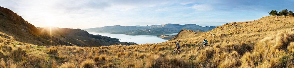 A young man and a women mountain biking on the Port Hills in Christchurch. Lyttelton Harbour is in the background.