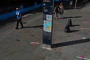 Ten weeks after the UK went into Coronavirus pandemic lockdown, the Office for National Statistics reveal that the total death toll has passed 50,000 covid-19 victims, a man wearing a face shield and a social distance t-shirt walks past distance markings on the pavement outside a Post Office in the borough of Southwark which ensure queues of daytime customers keep to within lockdown rules, on 2nd June 2020, in London, England.