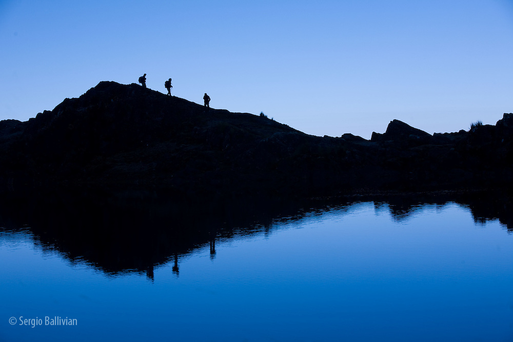 Trekkers are reflected in the cool waters of Chilata Lagoon outside the town of Sorata, Bolivia