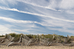 wooden beach fence in East Hampton, NY and a dramatic sky
