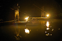 Men spearfishing at night from the bows of canoes in Mayalibit Bay.