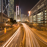 Asia, Peoples Republic of China, Hong Kong, Blurred traffic lights on brightly lit Queensway in city's Central Business District at evening on summer night