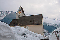 Old church against a snowy mountain background in Elm, Switzerland.