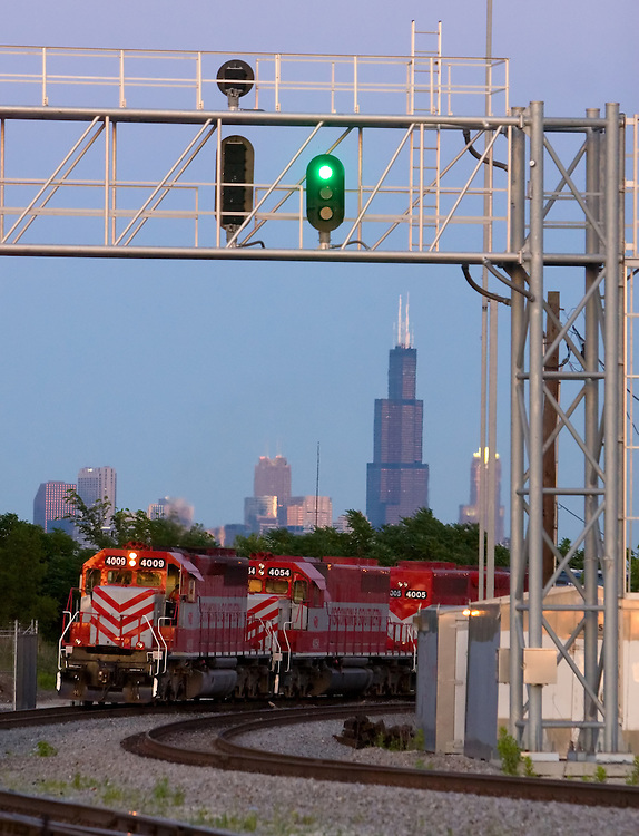 A Wisconsin & Southern Railway freight train rounds a curve on the west side of Chicago, IL, as the famous Sears Tower stands in the background.