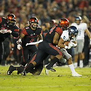 18 November 2017:  The San Diego State football team hosts Nevada Saturday night. San Diego State Aztecs linebacker Kyahva Tezino (44) and linebacker Ronley Lakalaka (39) bring down Nevada Wolf Pack running back Jaxson Kincaide (5) for a loss in the first quarter. The Aztecs lead 21-14 at the half. <br /> www.sdsuaztecphotos.com