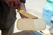 showing cheese piece before cutting farmers market South France